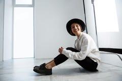 Сидеть молодой красивой девушки смеясь над на поле над белой стеной Стоковое Изображение