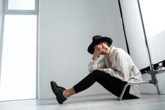 Сидеть молодой красивой девушки смеясь над на поле над белой стеной Стоковое Фото