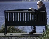 Сидеть на скамейке в парке Стоковое Изображение
