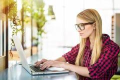 Сидеть на столе печатая на ее портативном компьютере в офисе, взгляд молодого женского предпринимателя работая от стороны Стоковая Фотография
