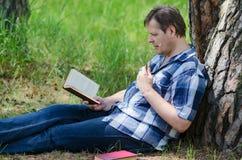 Сидеть около хобота старого человека сосны читает книгу Стоковые Изображения