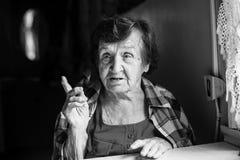 Сидеть пожилой женщины говоря на таблице Стоковое фото RF