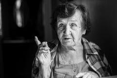 Сидеть пожилой женщины говоря на таблице Стоковые Фотографии RF