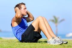 Сидеть-поднимает - тренировка человека фитнеса сидит вверх снаружи Стоковая Фотография RF