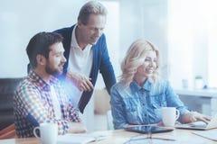 Сидеть положительного офиса работая на таблице Стоковое Изображение