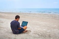 Сидеть с компьютером на пляже стоковые изображения rf