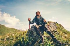 Сидеть человека путешественника ослабляя с trekking поляками Стоковая Фотография
