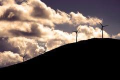 Силуэты ветротурбины на холме Стоковая Фотография RF