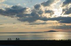 Силуэты велосипеда побережьем Стоковое фото RF
