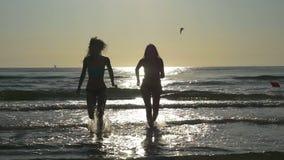 Силуэты 2 влажных женщин приходя из моря в замедленном движении сток-видео