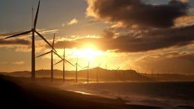 Силуэты генераторов энергии ветротурбины на бурной береговой линии океана на заходе солнца видеоматериал