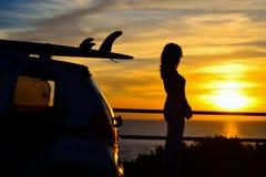Силуэты девушки и surfboard на заходе солнца Стоковые Изображения