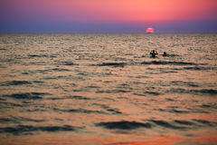 Силуэты детей играя в волнах на заходе солнца Стоковое фото RF
