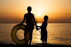 Силуэты детей на пляже Стоковые Изображения