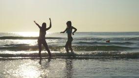 Силуэты 2 женщин танцуя на береге пляжа сток-видео