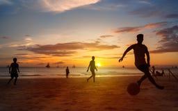 Силуэты захода солнца играя футбол пляжа Стоковая Фотография