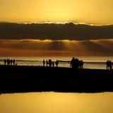 Силуэты захода солнца пляжа Стоковое Изображение