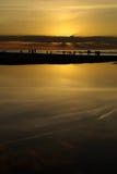 Силуэты захода солнца пляжа Стоковые Изображения