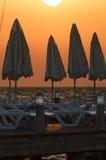 Силуэты зонтиков пляжа и loungers солнца в заходе солнца Стоковое Фото