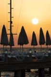 Силуэты зонтиков пляжа и loungers солнца в заходе солнца Стоковые Фото