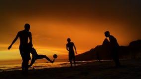Силуэты играя футбол Рио-де-Жанейро Бразилию пляжа сток-видео
