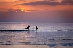 Силуэты игр детей на пляже Стоковые Изображения RF