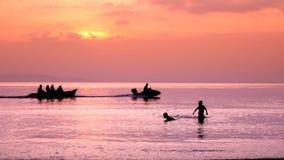 Силуэты игр детей на пляже Стоковое Фото