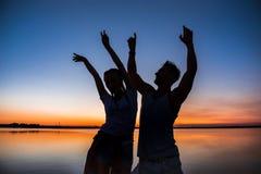 Силуэты ликования молодых красивых пар отдыхая на восходе солнца около озера Стоковая Фотография