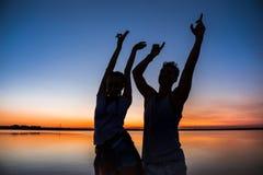 Силуэты ликования молодых красивых пар отдыхая на восходе солнца около озера Стоковое Изображение