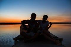 Силуэты ликования молодых красивых пар отдыхая на восходе солнца около озера Стоковое фото RF
