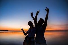 Силуэты ликования молодых красивых пар отдыхая на восходе солнца около озера Стоковое Фото