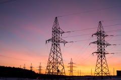 Силуэты линий электропередач, тема экологичности силуэты на небе захода солнца Опоры силы Стоковые Фото