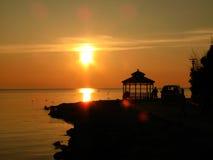 Силуэты и заход солнца пляжа Стоковая Фотография