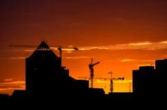 Силуэты и краны здания на заходе солнца Стоковое фото RF