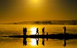 Силуэты и отражать на поверхности воды людей Стоковое Фото
