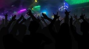 Силуэты концерта толпятся при руки поднятые на диско музыки Стоковая Фотография RF