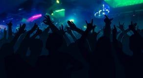 Силуэты концерта толпятся при руки поднятые на диско музыки Стоковые Изображения