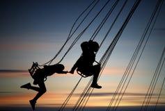 Силуэты маленьких девочек имея потеху на carousel Стоковые Изображения RF