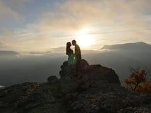 Силуэты молодых пар стоя на горе и смотря друг к другу на красивой предпосылке захода солнца Влюбленность парня Стоковое фото RF