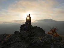 Силуэты молодых пар стоя на горе и смотря друг к другу на красивой предпосылке захода солнца Влюбленность парня Стоковое Фото