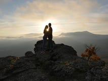 Силуэты молодых пар стоя на горе и смотря друг к другу на красивой предпосылке захода солнца Влюбленность парня Стоковые Фотографии RF