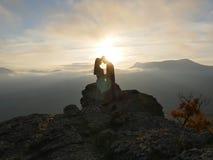 Силуэты молодых пар стоя на горе и смотря друг к другу на красивой предпосылке захода солнца Влюбленность парня Стоковая Фотография RF