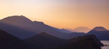 Силуэты наслоенных гор на заходе солнца, ландшафте природы Стоковые Изображения