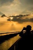 Силуэты на заходе солнца на взморье Стоковое Изображение