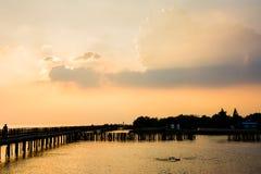 Силуэты на заходе солнца на взморье Стоковые Фотографии RF