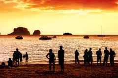Силуэты неизвестных людей наблюдая красный заход солнца Стоковые Изображения
