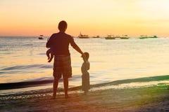 Силуэты отца и детей на пляже на заходе солнца Стоковая Фотография RF