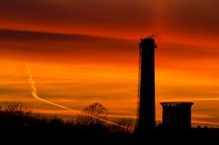 Силуэты промышленных зданий на заходе солнца Стоковое Изображение RF