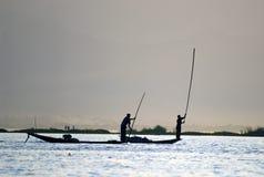 Силуэты рыболова на заходе солнца. Стоковое Изображение