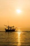Силуэты рыболовов удя в шлюпке стоковое изображение